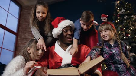 ded : Portrait shot of african boy in the santa claus costume reading book with kids.