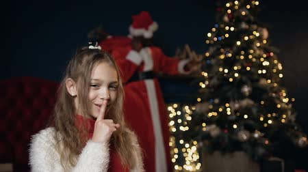 santaclaus : Little cute girl put finger on her lips asking to be quieter while santa claus putting gift. Stock Footage