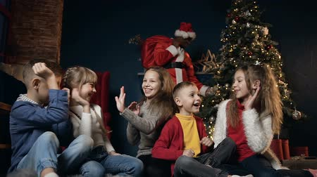 ded : Happy cute kids playing, laughing and giving five on the background with african man in the santa claus costume. Stock Footage