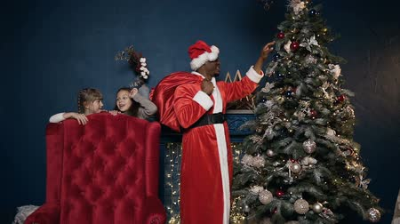 littlegirl : Little cute girls spying and hiding behind chair while african man in santa claus costume putting toy on the Christmas tree.