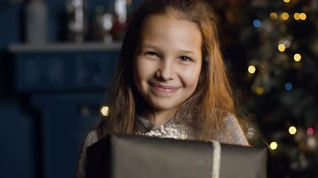 longhair : Close up shot of cute girl holding present and looking on camera on the christmas tree background. Stock Footage