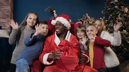 darovat : African man in santa claus costume and cute kids waving to the camera.