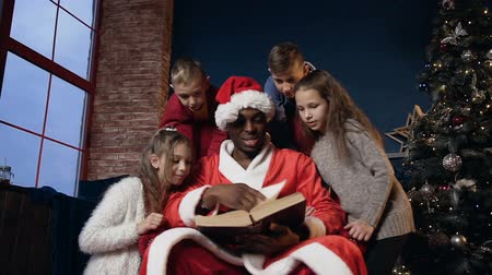 ded : Cute santa claus in funny hat reading book with kids.