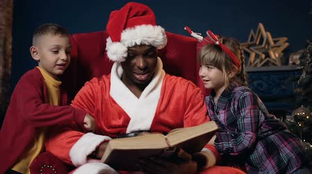 santaclaus : Portrait shot of santa claus in red hat reading book with two kids.