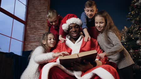 santaclaus : Santa claus in red hat sitting in the chair and reading book with four happy kids. Stock Footage