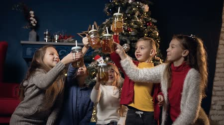 ded : Cute five children cheers cup of tea on the Christmas tree background in cozy room.