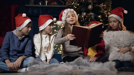 poblíž : Beautiful kids reading book sitting near christmas tree.
