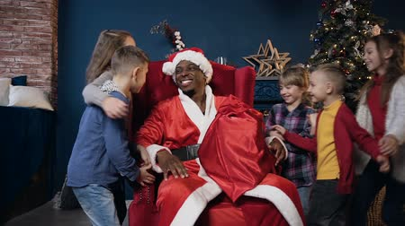 dát : Cute african man in santa claus costume sitting on the chair and holding the gift while five kids running and hugging him.