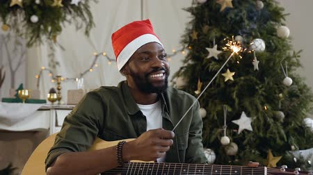 senta : Handsome afro american guy with guitar and bengal light happy is sitting on the floor in a glittering golden confetti on the background of a Christmas tree and christmas decorations