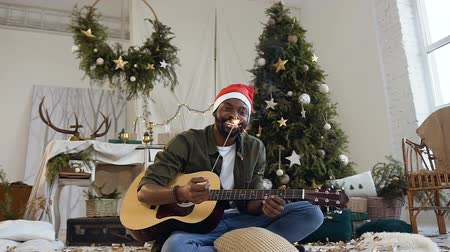 bengálsko : Happy african guy with guitar and bengal light sittingon the floor in a glittering golden confetti on the background of a Christmas tree and christmas decorations