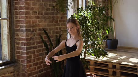 ballroom : Young beautiful ballerina dressed in black tutu trains gracefully in pointe ballet shoes in ballroom. Young charming ballerina practice ballet moves at the ballet school
