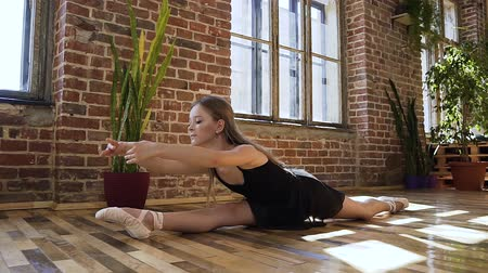 esneme : Cute teenage girl practices stretching in a modern ballerina school. Professional ballerina, healthy lifestyle. Yoga gymnastics. Modern sport school interior on the window and brick wall background