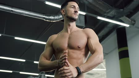 kulturystyka : Attractive young man without t-shirt rub his hands on the gym background.