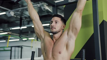 lift ups : Attractive young man doing crunches on horizontal bar in the gym.