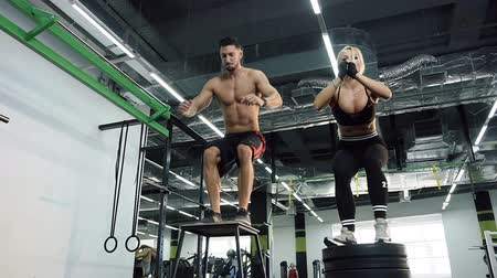 biceps : Sport man and woman jumping up and down on the chair on the gym background. Stock Footage