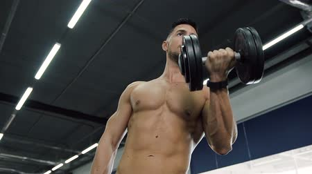aerobic : Attractive fit man without t-shirt making exercises for hands with dumbbells.