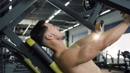 aerobic : Young sport man pumping arms muscle using sports exercise machines in the gym. Wideo