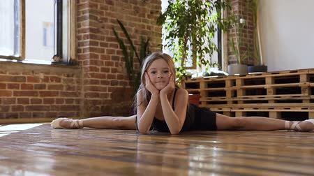esneme : A young charming ballerina in black tutu making twine in the dancing hall. Slim dancer ballerina in black tutu practicing stretching twine at dance school Stok Video