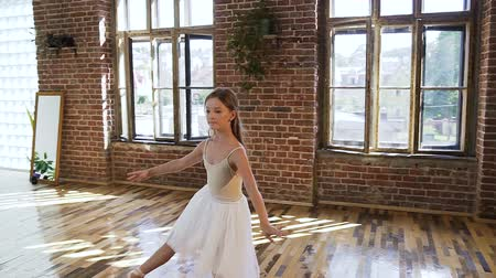 terlik : Ballet dancer dressed in white tutu perform classic ballet dance, she trains gracefully in pointe ballet shoes in ball school. Graceful charming ballerina practicing ballet movements at the dance-hall Stok Video