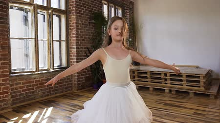 sukénka : Graceful young ballerina in white dress tutu and pointe shoes performed ballet dance. Young ballerina is doing different ballet element near the big window and red brick wall