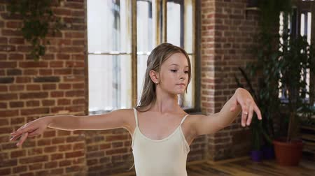 ustalık : Young ballet dancer dancing a classical ballet in pointe shoes and tutu on the background of a large window and red brick wall. Elegant ballerina in pointe shoes and in a white fluttering dress