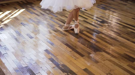 delgado : Slender ballet dancers feet in white ballet shoes practices ballet dance on the wood floor. Young ballerina in white pointe shoes dances on tiptoe Stock Footage