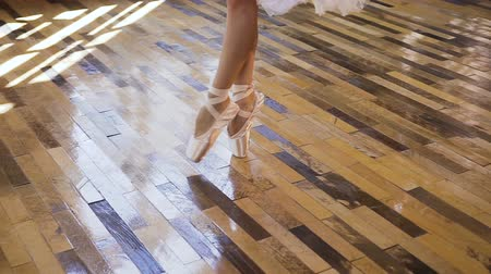 ballroom : Young ballet dancer in white ballet shoes and skirt practices ballet dance on the wood floor. Young ballerina in white pointe shoes dances on tiptoe at ballet school