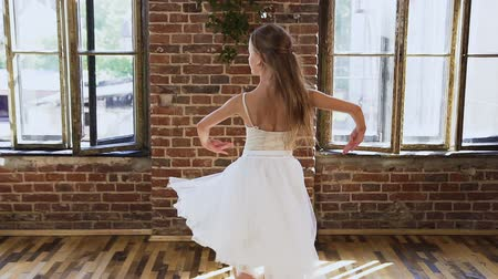 sukénka : Graceful teen girl in white dress tutu practicing classic elements of ballet in the ballet school. Graceful sensual ballerina in white dress dancing elements of classical or modern ballet