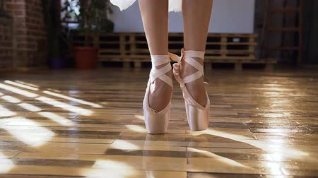 tiptoe : Close-up of ballerina graceful feet in ballet shoes dancing ballet elements on wood floor at ballet class. Dancing ballerinas feet in a dance-hall