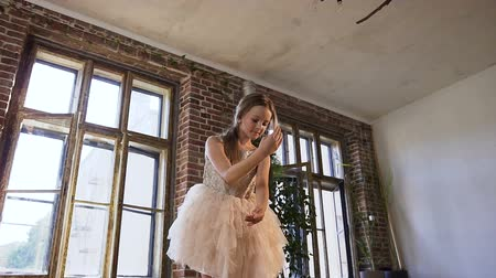 тапочка : Ballet dancer dressed in tutu perform classic ballet dance, she trains gracefully in pointe ballet shoes in ball school. Graceful charming ballerina practicing ballet movements at the loft dance-hall