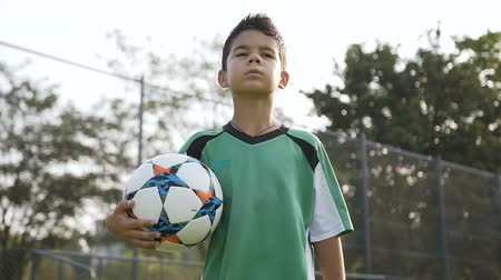 satisfait : Portrait of sport boy with soccer ball in the hand walking on the field.