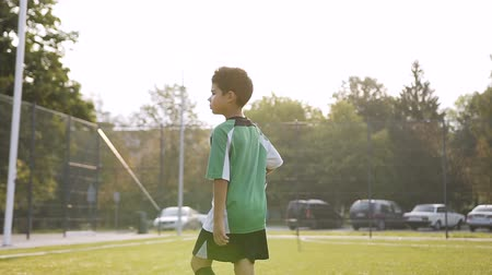 tevreden : Young football player walking with soccer ball.