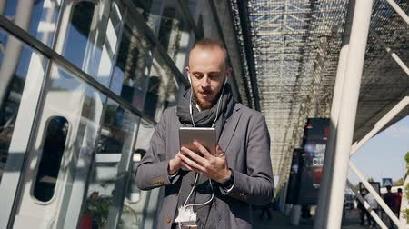 netbook : Happy caucasian businessman using tablet device while standing near big office centre windows outdoors. Young man in headphones scrolling pages, tapping on touchscreen, checking financial charts at tablet computer Stock Footage