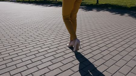 emancipation : Young businesswoman in suit and shoes with heels goes to the city. Close-up of female slim feet walking through the downtown