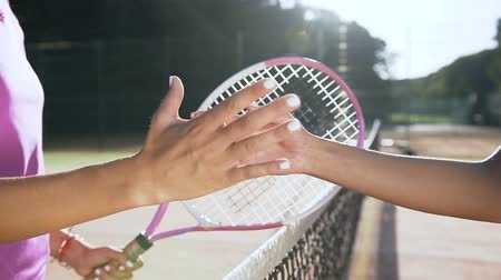 hizmet etmek : Close up shot of female tennis players shaking hands over the tennis court net.