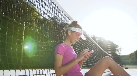 spotswear : Sport girl sitting on a tennis court near net and using smart phone.