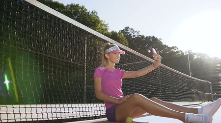spotswear : Attractive young woman sitting on a tennis court near net while taking selfie on smart phone.