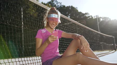 spotswear : Young attractive woman using smart phone while relaxing on a tennis court. Stock Footage