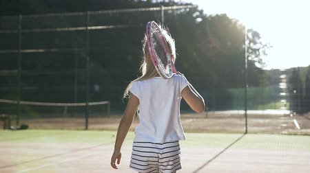 teniszütő : Little girl with tennis racket walking on the court. Stock mozgókép