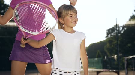 čepice : Young female coach with little girl during tennis training.