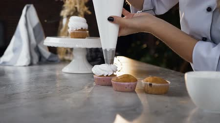 kaplanmış : Woman hands using pastry bag to putting cream on the cake.