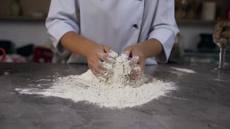 grain bread : Confectioner kneading dough while mixing water with flour on the table.