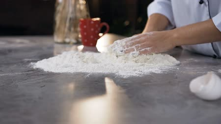 taneli : Woman hands kneading dough while mixing water with flour on the table. Stok Video