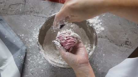 squeeze : Top view of chef hands decorating marshmallow using powdered sugar from the plate.