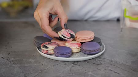 kaplanmış : Female baker putting halves of macaroon into the plate.