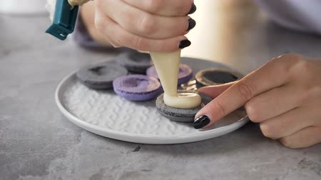 kaplanmış : Close up shot of woman hands using pastry bag to putting cream on the half of macaroon.