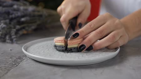 mandle : Side view of woman hands cutting macaroon on the halves using knife.