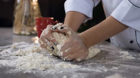 taneli : Side view of young confectioner kneading dough with flour on the table.