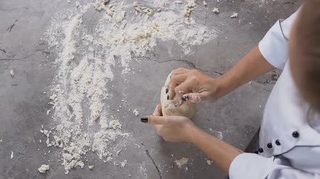 pekař : Young confectioner kneading dough with flour on the table.