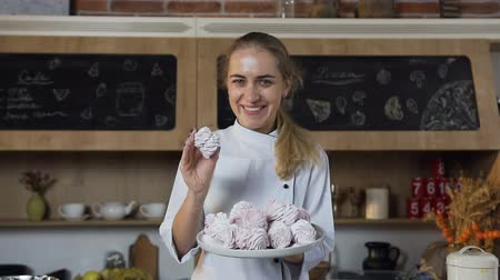 candy : Beautiful female baker smiling to the camera with a plate of marshmallows.
